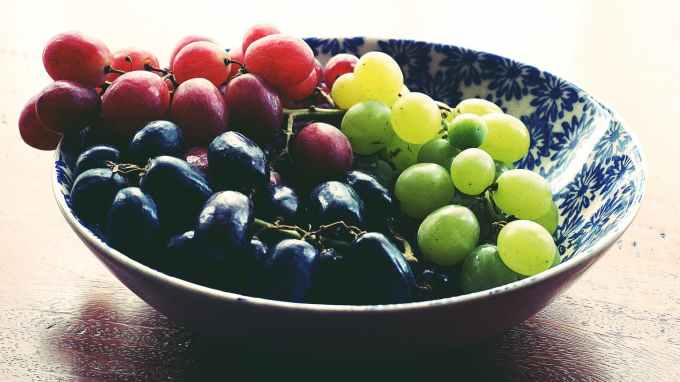 red black and green grapes in round blue and white floral ceramic bowl